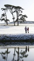A couple standing in a snow-covered field by a river. Trees in background.
