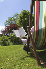 A person sitting in a deckchair, reading.