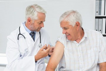 Doctor injecting senior male patient