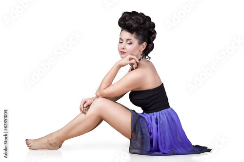 Attractive young woman in beautiful dress sitting. Isolated