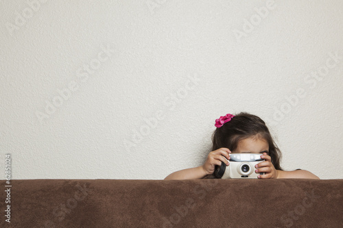 A young three year old girl crouching behind a sofa, with a toy camera, taking a picture.
