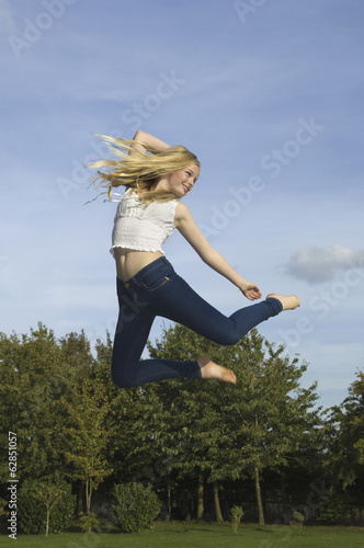 Teenage girl with long blond hair jumping in the air.