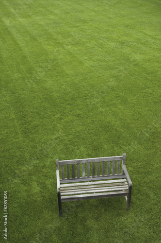 A wooden bench on a grass lawn.
