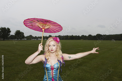 A young woman wearing a laced basque and frilly bloomers, striped stockings and suspenders. Holding a paper sunshade umbrella. A carnival circus outfit.
