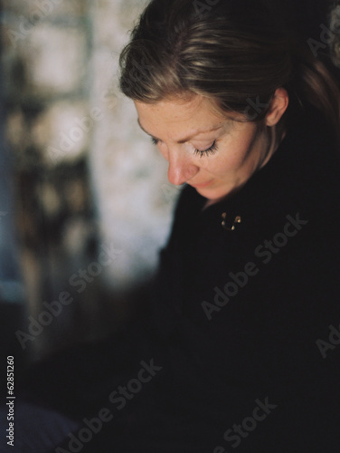 A woman wearing a black coat, looking down in a pensive mood.