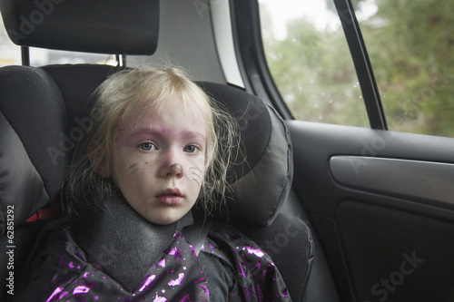 A young girl in a car seat in Halloween costume.