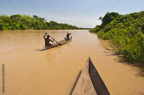 Men paddling canoe upstream, Black Volta river, Ghana