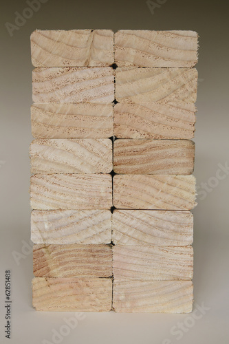 Stack of sawn prepared timber, spruce wood planks or studs, for use. Treated wood in traditional 2 by 4 measured cut shapes. Cut ends.