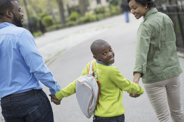 A New York city park in the spring. A boy with a bookbag, holding hands with his mother and father.