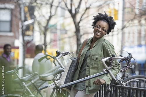 Outdoors in the city in spring. An urban lifestyle. A woman leaning against a railing beside a bicycle rack.