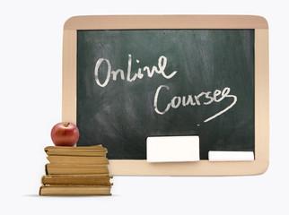Blackboard with Online Courses written on it, books,apple