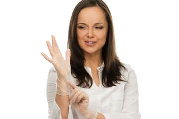Young positive brunette doctor putting on latex gloves