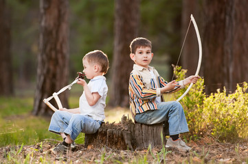 Little boys in the woods with bows and arrows