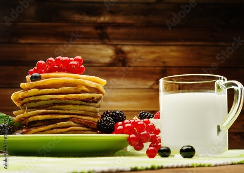 Healthy breakfast with pancakes, fresh berries and milk