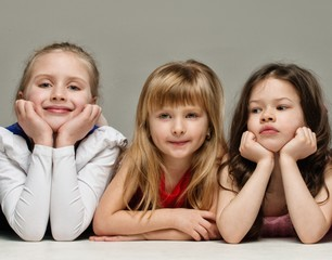 Three little girls isolated on grey background