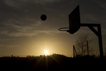 Silhouette of a basketball in mid air during sunset