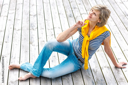 Woman sitting on the wooden floor outdoors