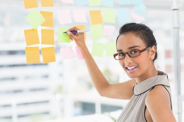 Smiling designer writing on sticky notes on window looking at