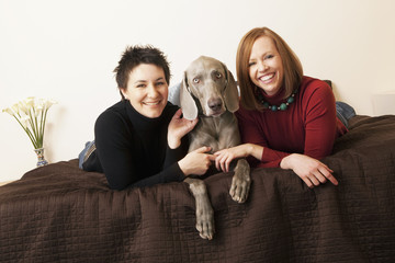 A same sex couple, two women with their Weimaranar pedigree dog between them.