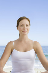 A spa treatment centre. A young woman seated in a relaxed pose on the beach.