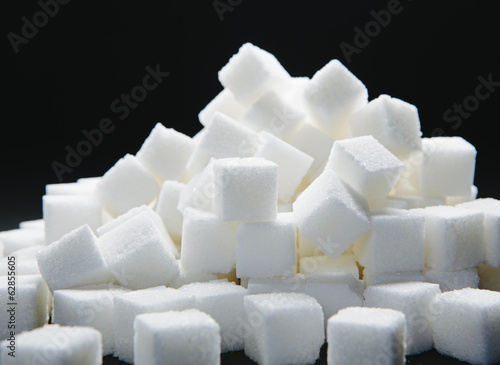 Pile of sugar cubes, black backdrop