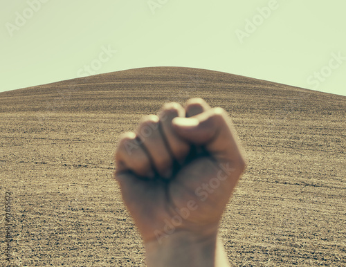 A hand bunched up and making a fist, in a gesture of defiance or determination, against the background of a ploughed field and farmland.