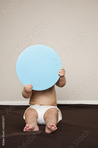 A young 8 month old baby boy wearing cloth diapers, hiding behind a large blue disc.