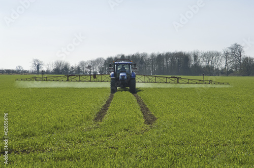 Tractor and crop-sprayer in field.
