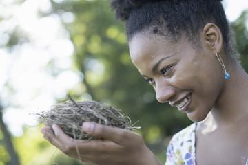 A woman holding a bird nest in her hands.