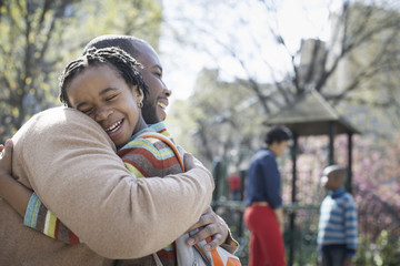 A New York city park in the spring. A family together. A father hugging his son.