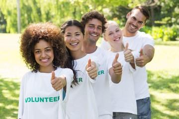 Confident volunteers gesturing thumbs up