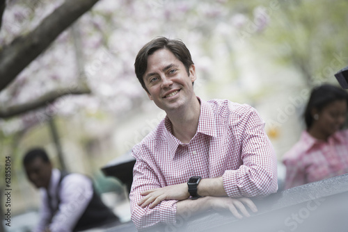 City life in spring. A man sitting outdoors in a city park. Looking at the camera and smiling.