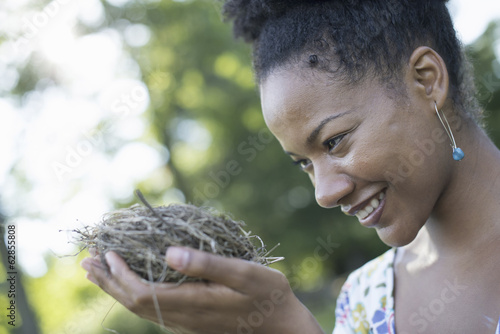 A woman holding a bird nest in her hands.