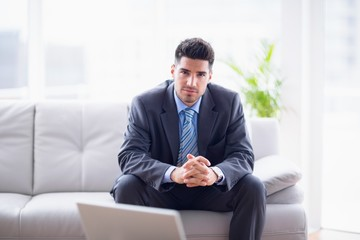 Happy businessman sitting on the sofa looking at camera