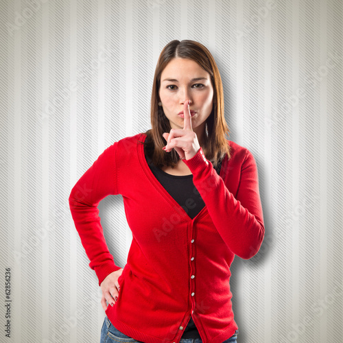 Young girl making silence gesture over textured background