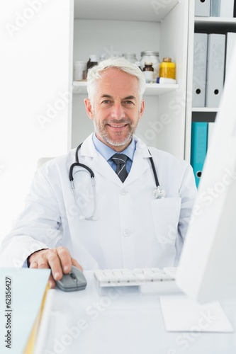 Confident male doctor with computer at medical office