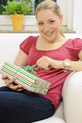 Frau packt Geschenk aus
