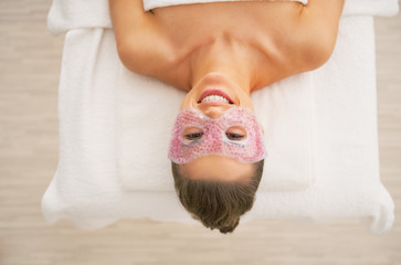 Happy young woman with eye mask laying on massage table