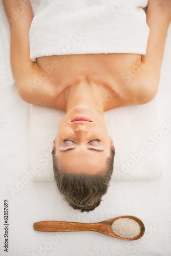 Relaxed young woman laying near spoon with salt
