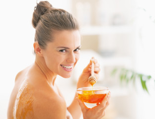 Smiling young woman enjoying honey spa therapy