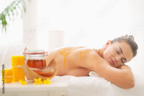 canvas print picture Relaxed young woman receiving honey spa therapy