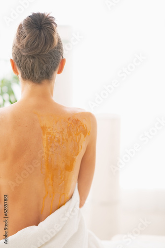 Young woman with back in honey. rear view