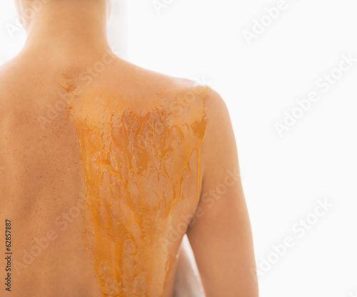 Closeup on young woman with back smeared in honey. rear view