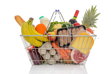 Shopping basket full of fresh food isolated on white.