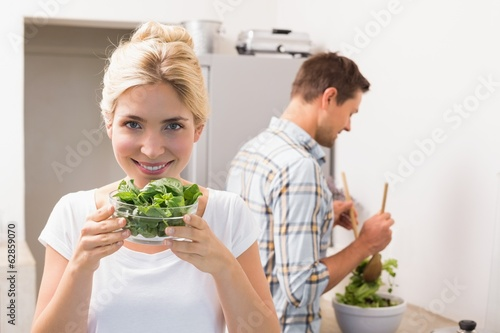 Woman holding bowl of leaves with man preparing salad in