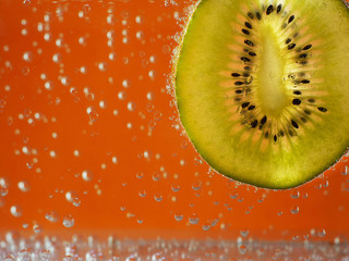 kiwi in aerated water on orange background