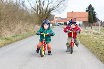 Two little twin toddler boys having fun on bicycles, outdoors