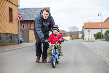 Young father teaching his 3 years old little son to ride a bike