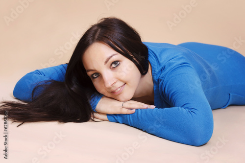Studio portrait of beautiful brunette lying on the floor