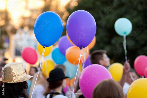 children hold colored balloons